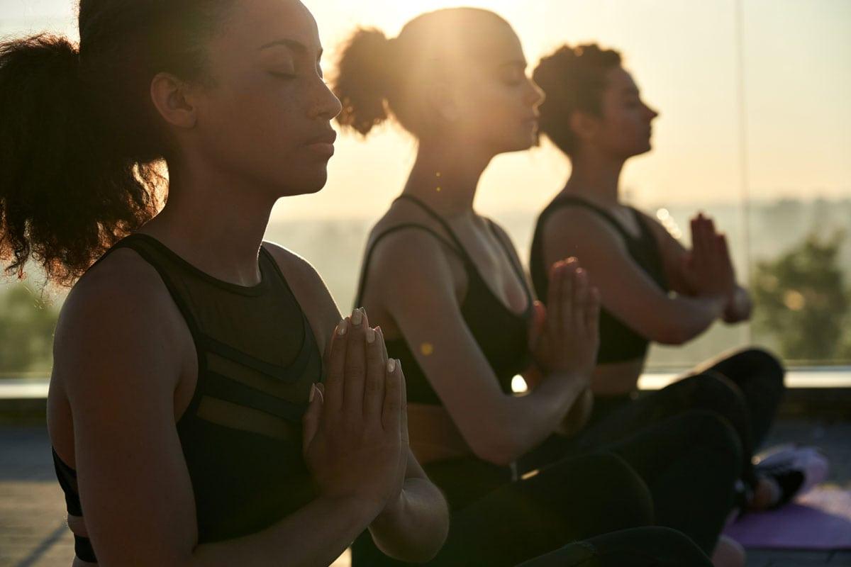 3 women meditating outdoor